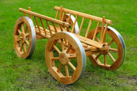 Decorative cart from pine wood on the green grass photo