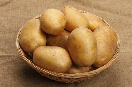 Several brown potatoes in a basket on a sacking