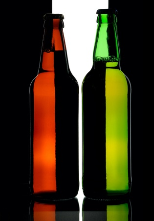Bottles of lager beer from green and brown glass, isolated on a black and white background. photo