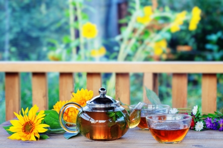 The Drinking of tea on dacha. Herbal tea in teapot and cup. Stock Photo