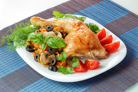 Fried chicken leg with vegetables and greens on a platter photo