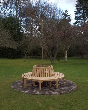 garden bench: Circular wooden bench in a garden Stock Photo