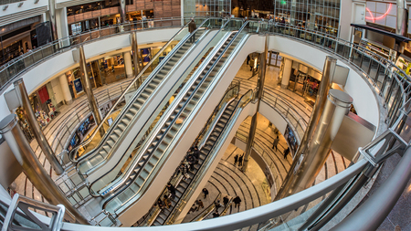 Fish eye view of escalators with people rushing through in a shopping centre in Canary Warf, London