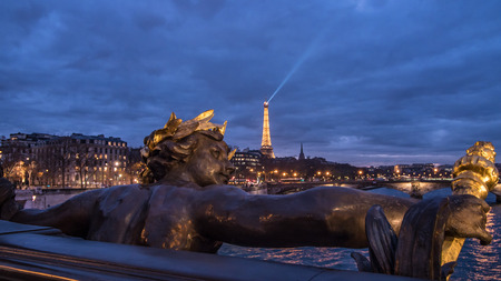 View of a statue on Alexandre III bridge in Paris and the Eiffel tower at sunset