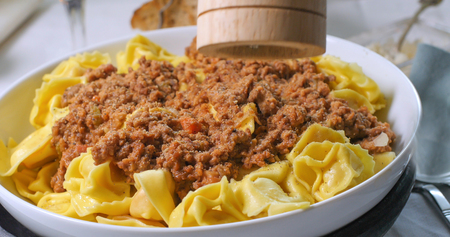 sprinkling: Sprinkling black pepper over delicious steamy tortellini in bolognese sauce