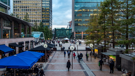View of people rushing from work with several clocks in the Docklands, financial centre in London