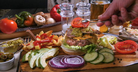 adding: Adding a slice of tomato over a delicious cheesburger with beer and French fries