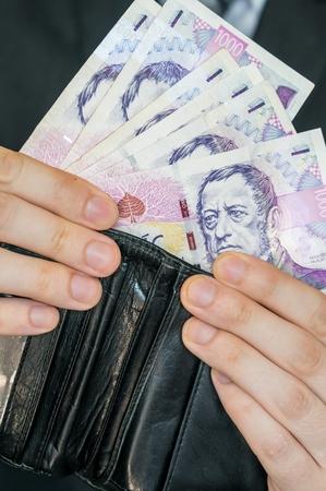 billfold: Man holds Czech money.