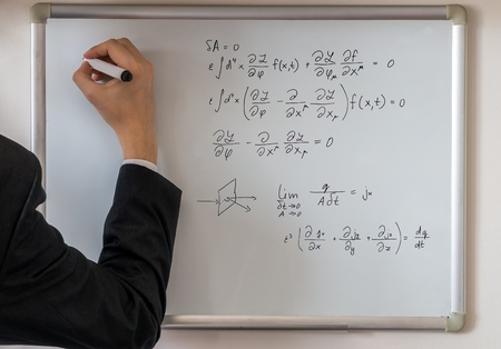 equations: Theacher solves math equations on whiteboard.