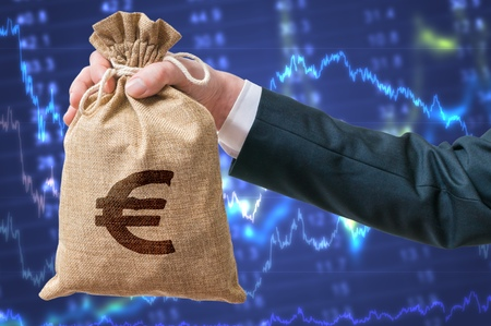 Economics of Eurozone. Businessman holds bag with money with Euro sign. Stock exchange and investment concept.