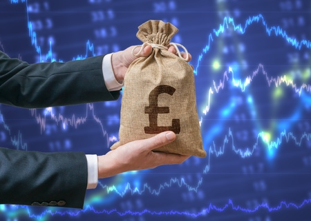 british man: Hands of business man holds bag full of money with British pound sign. Investment and stock exchange concept.