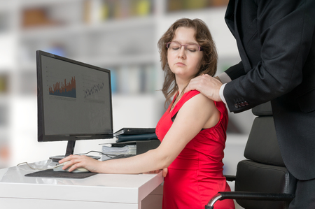 mobbing: Harassment at workplace. Boss or manager is touching shoulder of his secretary in office.