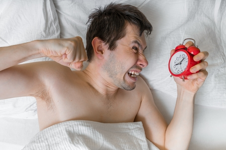 Young angry man is waking up and wants to damage his alarm clock with fist. Stock Photo