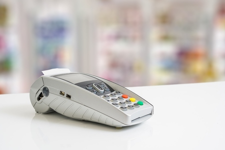 POS payment terminal on white table.