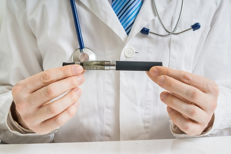 Doctor is analysing health effect of electronic cigarette or vaporizer.