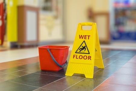 젖은 바닥의 노란색 플라스틱 기호를 경고합니다. 스톡 콘텐츠