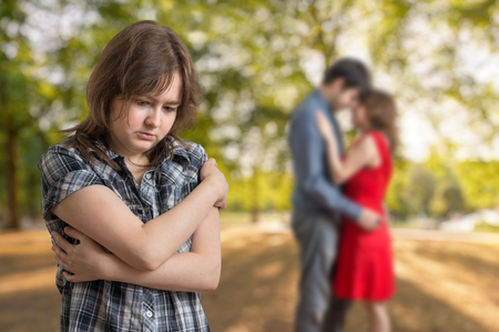 unfaithful: Young jealousy girl is seeing her boyfriend with other one girl. Stock Photo