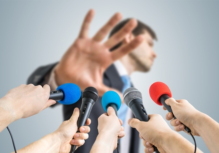 statesman: Many reporters are recording with microphones a politician who shows no comment gesture. Stock Photo