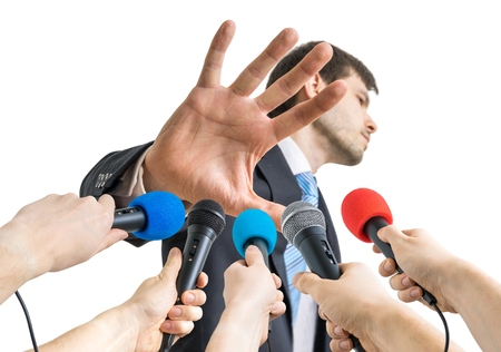 Many microphones in front of politician who shows no comment gesture.