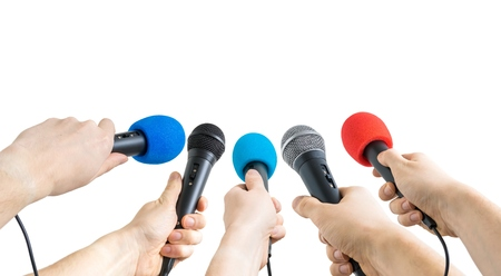 Journalism and conference concept. Many reporter hands hold microphones. Isolated on white background. Archivio Fotografico
