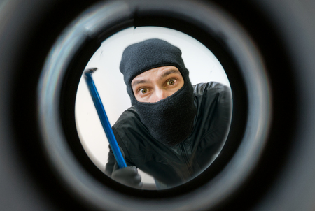 View through pipehole. Thief or burglar masked with balaclava is holding crowbar behind the door. Stockfoto