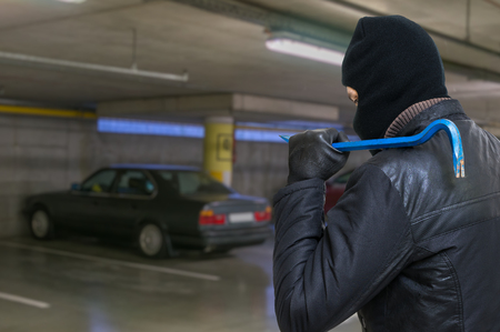 crowbar: Thief with crowbar is going to steal car from garage. Stock Photo