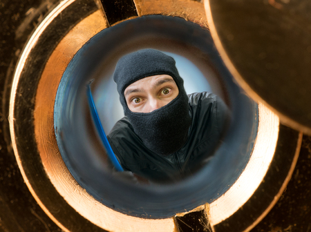 peephole: View through pipehole. Robber or burglar masked with balaclava behind the door.