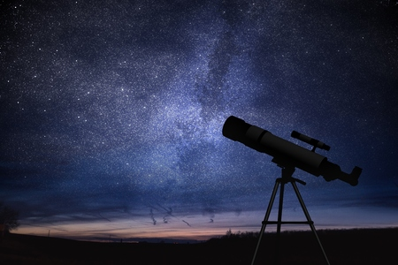 Silhouette of telescope and starry night sky in background. Astronomy and stars observing concept.