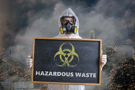 Ecology and pollution concept. Man in coveralls is warning against hazardous waste. Stock Photo
