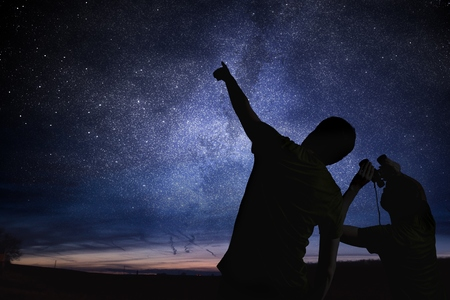 starry night: Silhouettes of people observing stars in night sky. Astronomy concept.