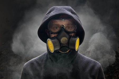 Apocalypse or armageddon concept. Man is wearing gas mask. A lot of smoke in background. Stockfoto
