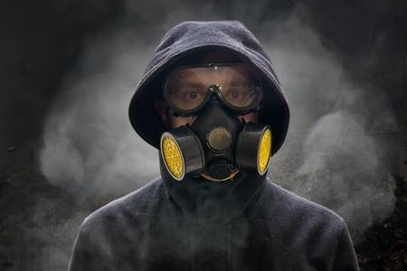Concepto de apocalipsis o armageddon. El hombre lleva una máscara de gas. Una gran cantidad de humo en el fondo. Foto de archivo