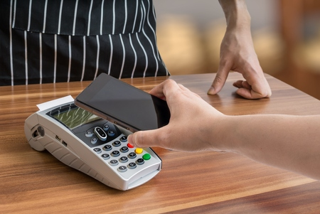 Customer is paying with smartphone in shop using NFC technology.