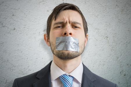 検閲の概念。若い男が彼の口にダクトテープで黙らせた。