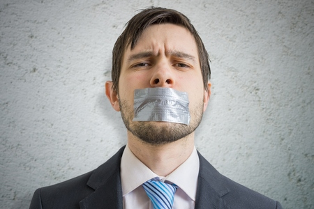 Censorship concept. Young man is silenced with duct tape over his mouth. Stok Fotoğraf