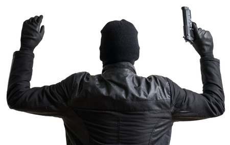 Burglar masked with balaclava is putting hands up and gives up. Isolated on white background.
