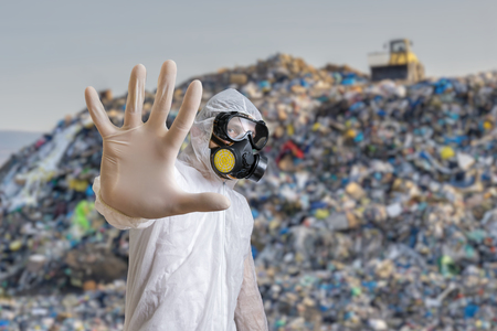 Man in coveralls is showing stop gesture. Garbage pile in landfill in background.