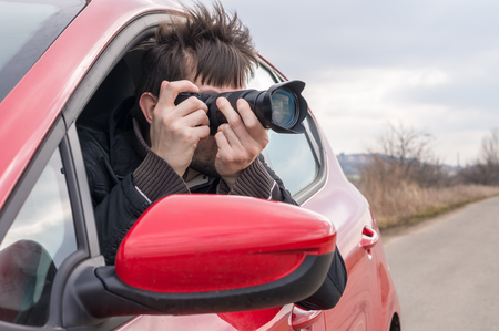 spying: Paparazzi is taking photo with camera from car.