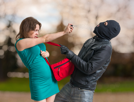 Self defense concept. Young woman is spraying with pepper spray on thief. Archivio Fotografico