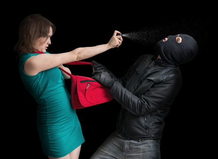 Self defense concept. Young couple is defending with pepper spray against thief in balaclava. Low key photo.