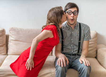 Shy man is surprised by kiss from woman sitting on sofa. Dating concept. Banco de Imagens