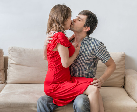 Young couple in love is sitting on sofa and kissing.