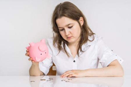 Young woman have no money. Her piggy money bank with savings is empty.