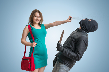 Self defense concept. Young woman is defending herself with pepper spray against robber with knife. Stock Photo