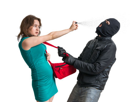 Self defense concept. Young woman is fighting with thief and using pepper spray. Isolated on white background.