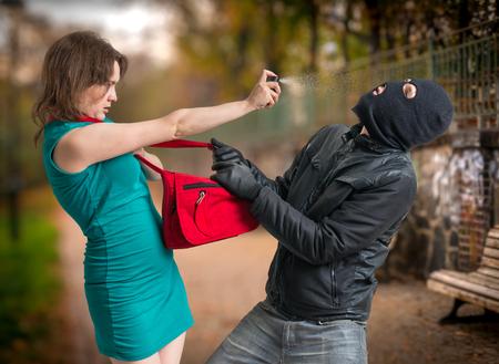 Concepto de autodefensa La mujer joven fue atacada por el hombre en pasamontañas y está utilizando el aerosol de pimienta. Foto de archivo