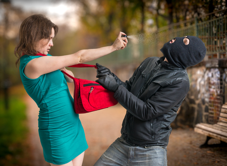 Self defense concept. Young woman was attacked by man in balaclava and is using pepper spray. Stock Photo