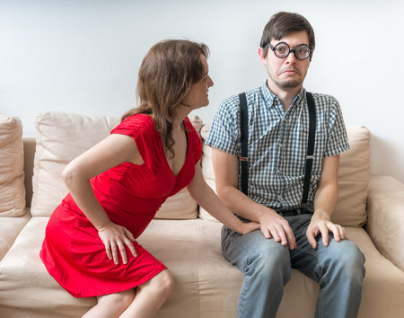 First date of a couple. Young woman is flirting with shy man sitting on sofa.