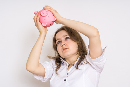 Young worried woman is looking on empty piggy money bank.