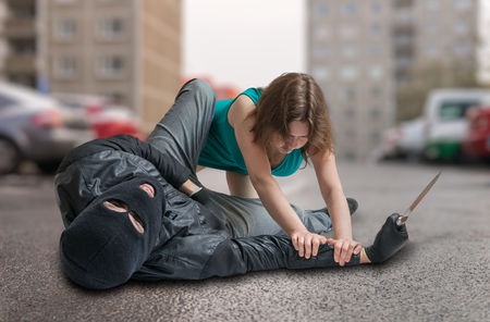 Young woman is fighting with thief on street. Self defense concept.